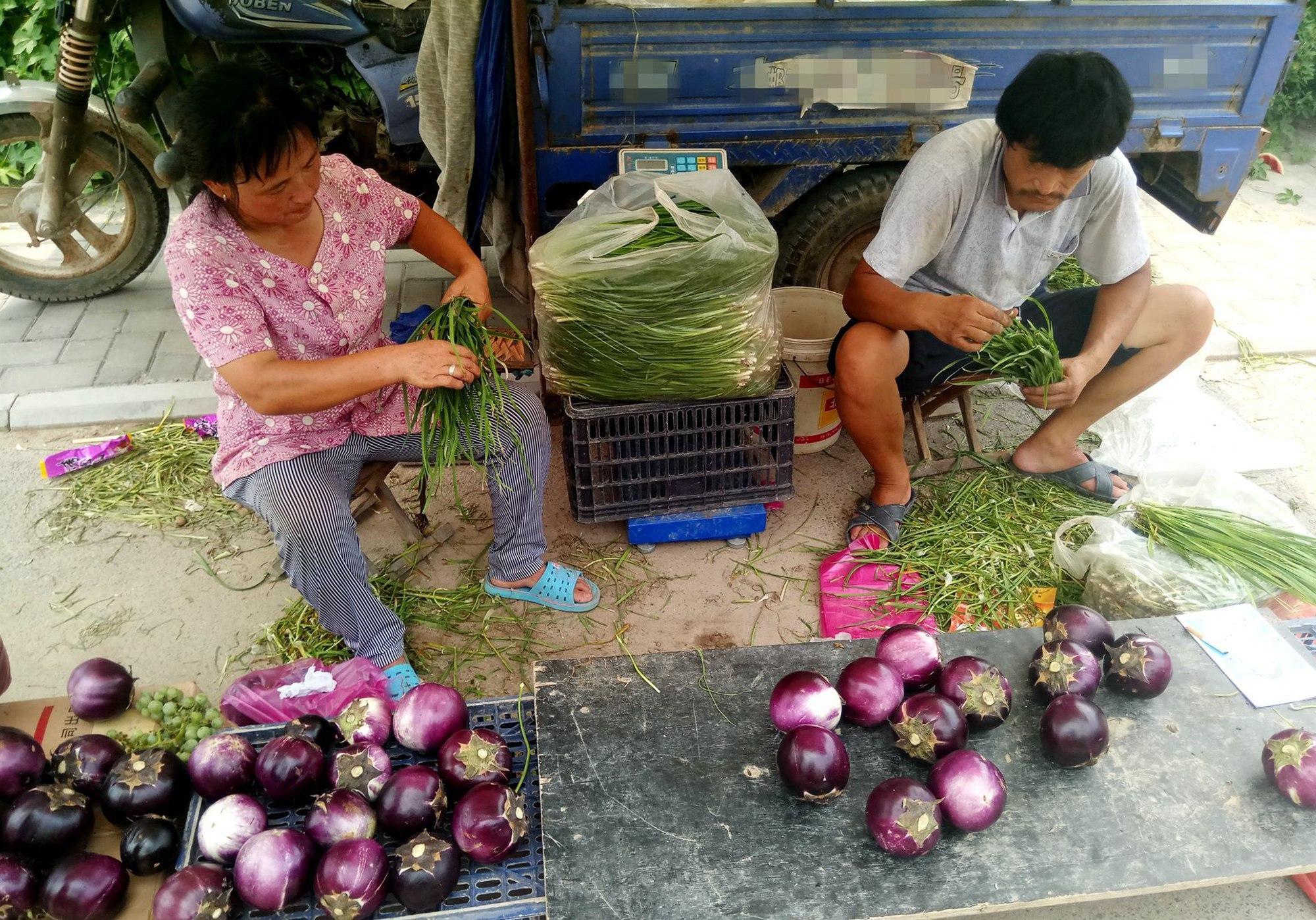 38度高温农民夫妻二人大集上卖韭菜,说出儿子没娶媳妇原因