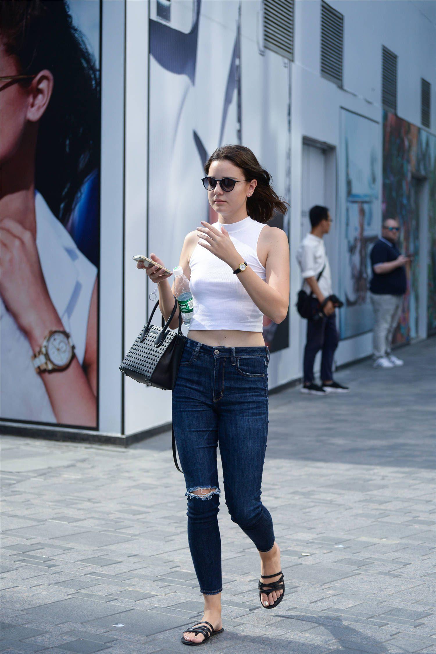 深蓝色紧身牛仔裤,却搭配一款拖鞋,换成高跟鞋会更美