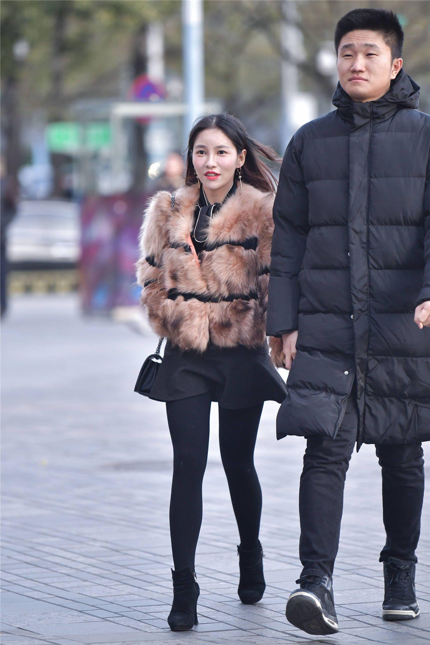 黑色打底裤搭配黑色的短裙,暖色的皮草,穿出冬季时尚味道
