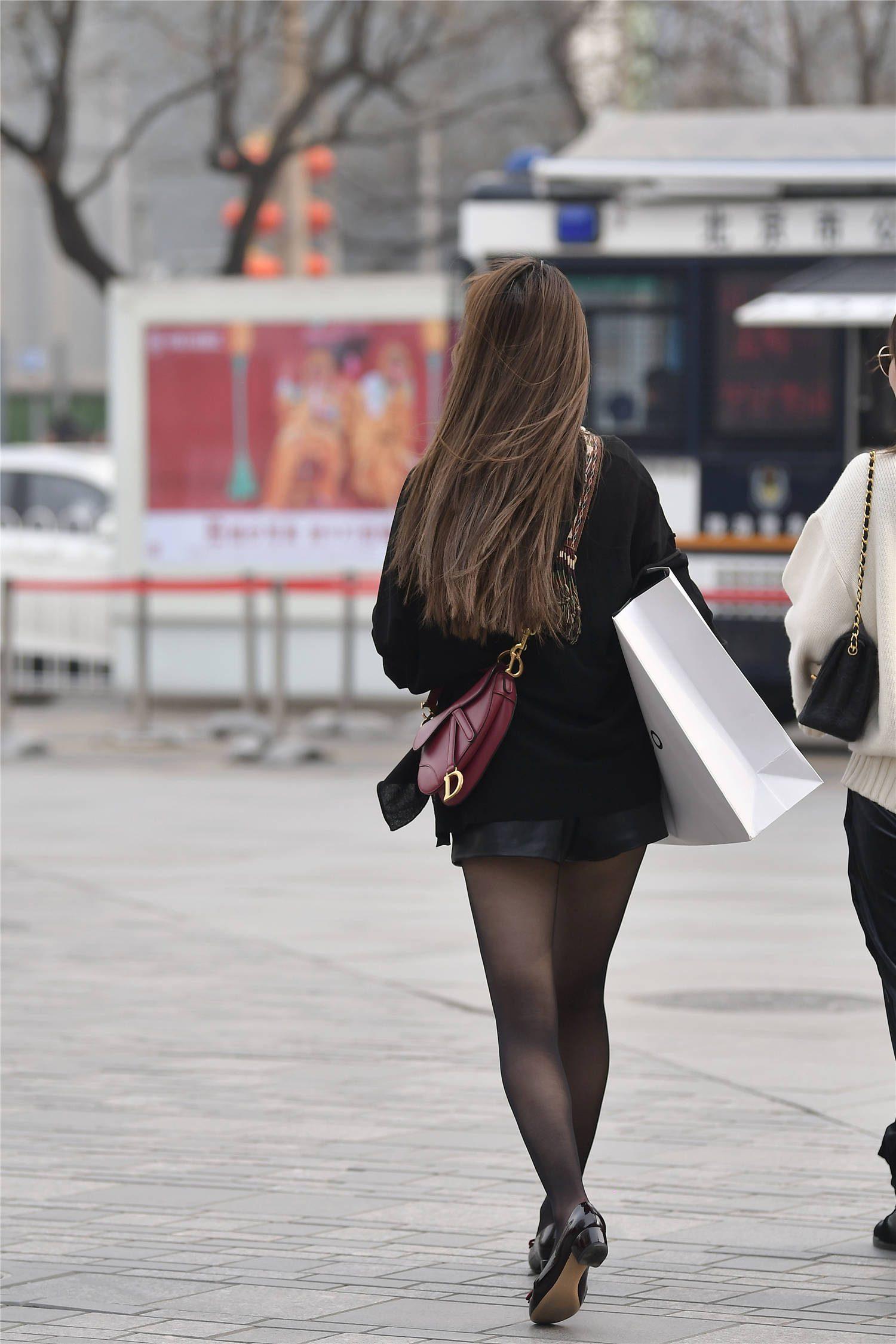 黑色丝袜受到时尚姑娘青睐,搭配皮质短裤,造型独特又不落俗套